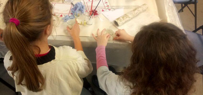 De jeunes bénévoles fabriquent des bougeoirs durant l'atelier parents/enfants pour le Téléthon