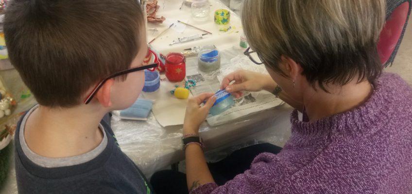 Des familles qui fabriquent des bougeoirs durant l'atelier parents/enfants pour le Téléthon
